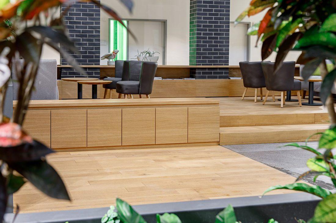 Schuster Innenausbau aus Salach – Bürogebäude mit Charme - Wartebereich Pflanzen und Eiche Einbaumöbel